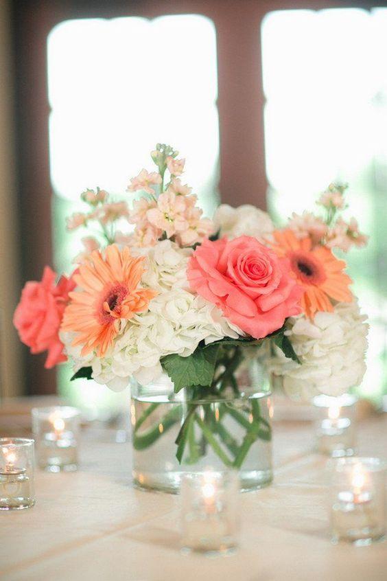 Simple y elegante centro de mesa en coral con hortensias y rosas.