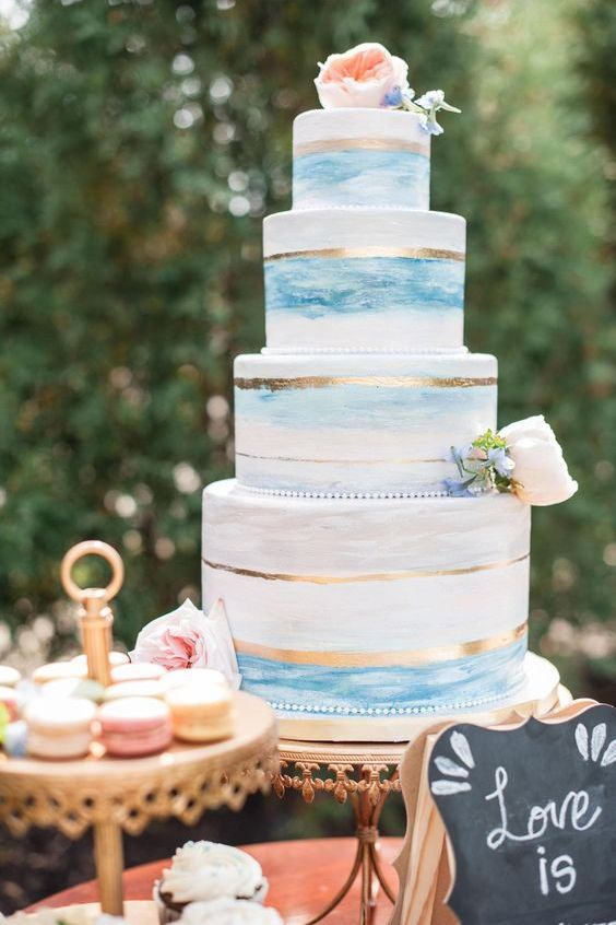 Four tiers of delicious seascapes! Wedding cake, blue watercolor paint, gold strip crowned by a Juliet garden rose. Wedding photographer: Stewart Imagery.