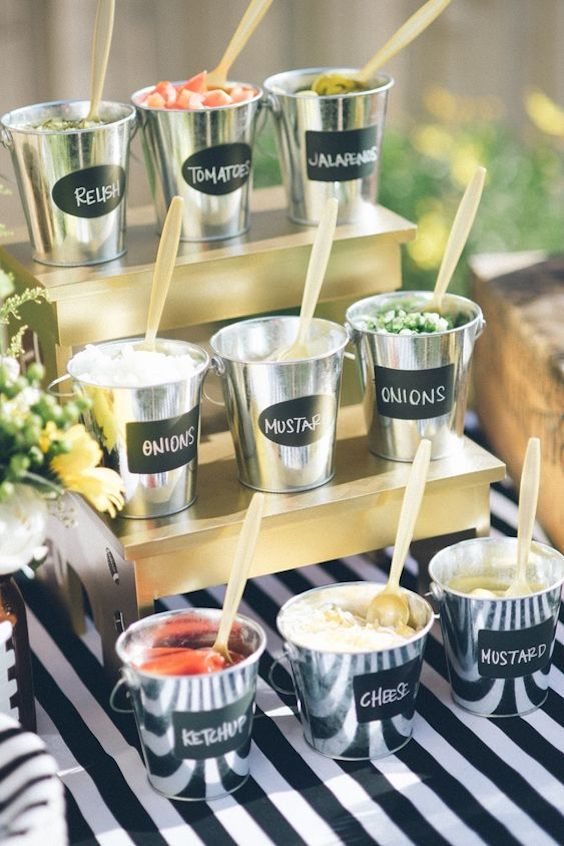 Show off all the condiments you could ever want for a hot dog, in foil lined metal buckets, labeled with chalk pens and placed on a small riser painted in gold spray paint.