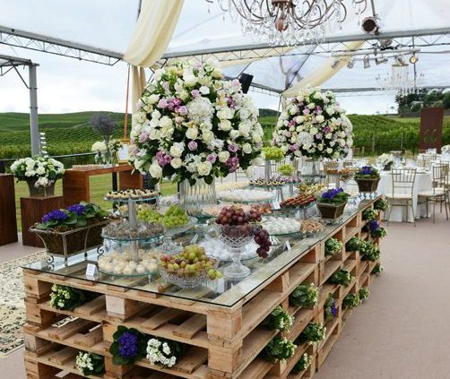 Una mesa de postres muy moderna hecha con paletas de madera. Pequeños ramitos de flores se asoman por los costados y el toque avant garde esta dado por el vidrio donde se apoyan los deliciosos postres.