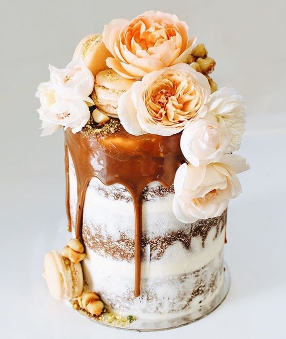 Modern drip wedding cake trends. Stunning and perfect for an intimate wedding or a very daring bride covered with flowers and macarons.