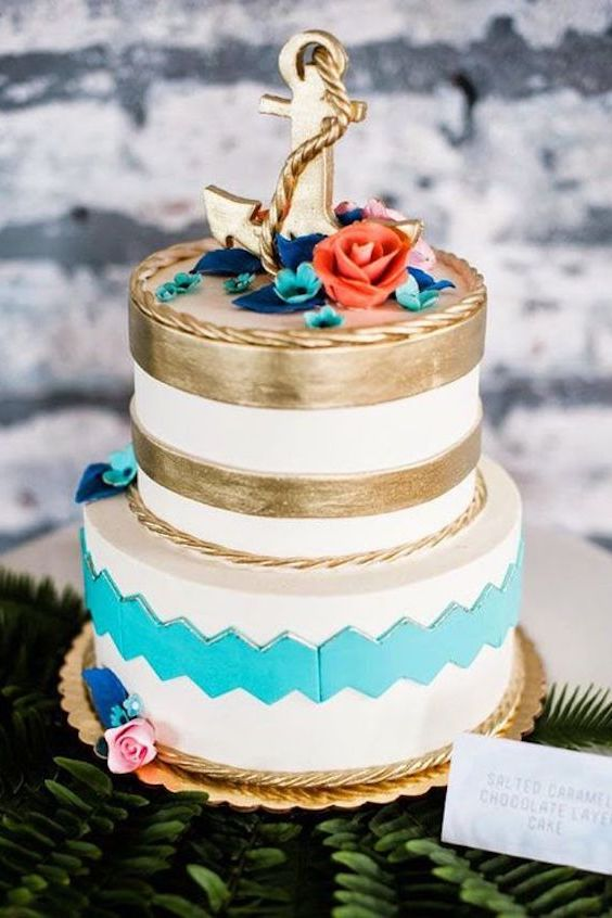A modern nautical wedding cake with gold leaf foil and ruffles in turquoise. The coral tone flower adds a perect pop of color. Salter caramel chocolate layer cake by Whipped Bakeshop. Photographer: George Weiss.