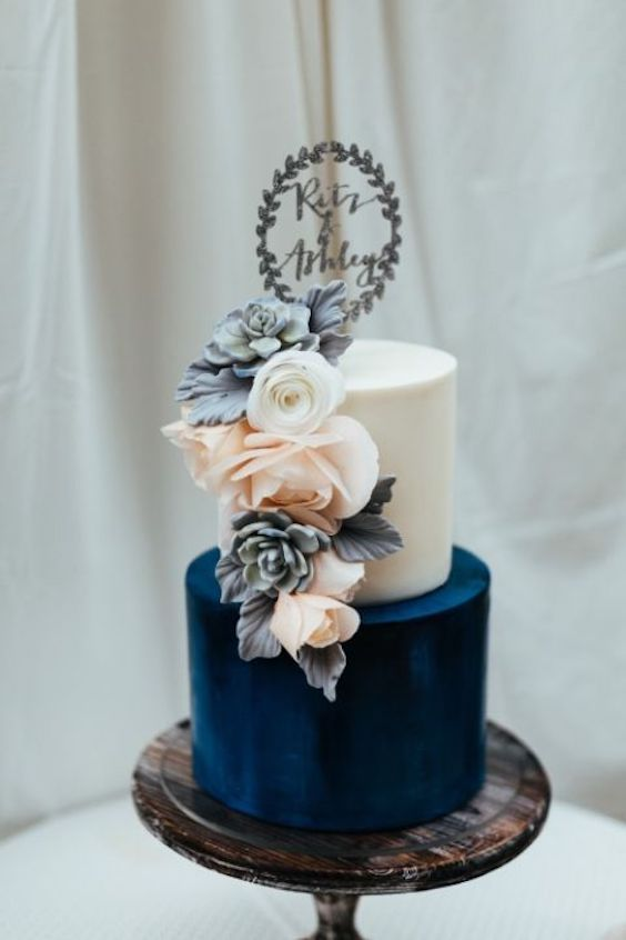 Stunning white and navy blue wedding cake featuring a cascade of roses.