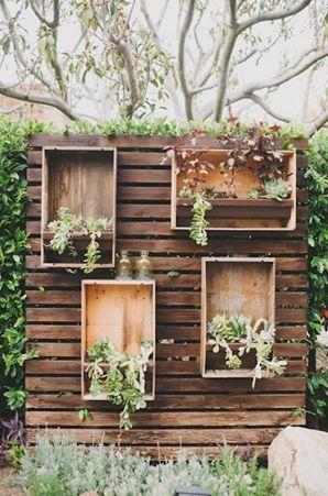 Un fondo sobre una paleta de madera con cajones, plantas y botellones antiguos. Tal como me gustaría que se vea mi propio jardín. Decoración con palets y cajones de madera.