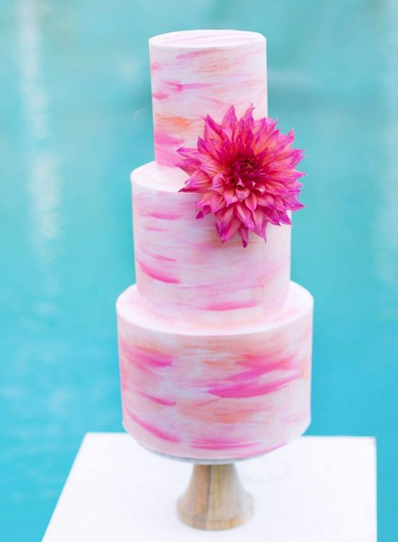 Imagine your beach wedding (or backyard summer wedding with a pool) with this three tiered pink and orange watercolor accented round cake. Love the big flower a simple yet bold statement. By Sweet Bakes.