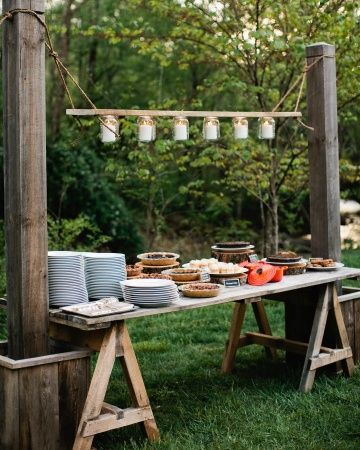 Rustic chic wedding dessert table over trestles and lighting built in with a row of hanging jars.