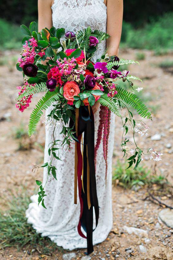Fuchsia, borravino y dorado se funden para lograr un look de boda boho. Ramo de novia con helechos y cintas en cascada. Foto: Amilia Photography.