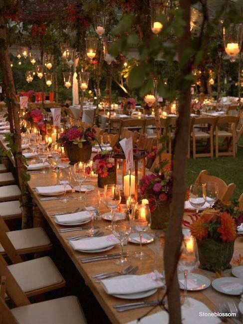 Bodas románticas en jardín. Velas, centros de mesa con flores y árboles con luces colgantes.