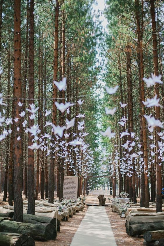 Grullas de papel sobre el camino central de bodas. Unos troncos es todo lo que precisas para una cemonia en un bosque encantado. Foto: Carolien and Ben.