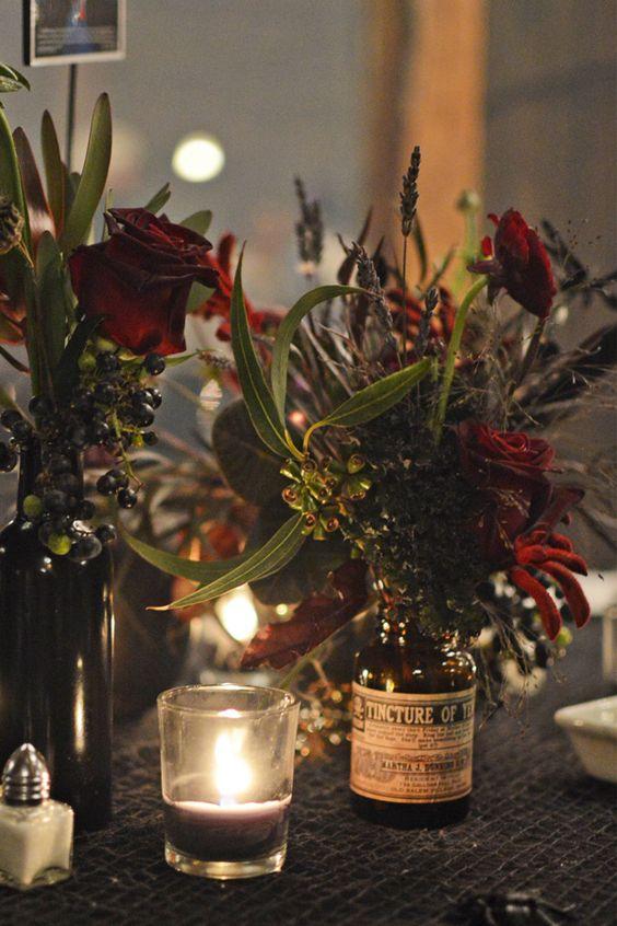 Centro de mesa hecho con una botella de farmacia antigua, flores en color marsala y ramas de eucalipto. Fotógrafo de bodas: Birke Photography.