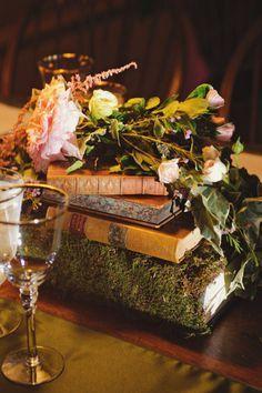 Agrega un acento de cuento de hadas a tu decoración de bodas con unos libros viejos cubiertos de musgo.