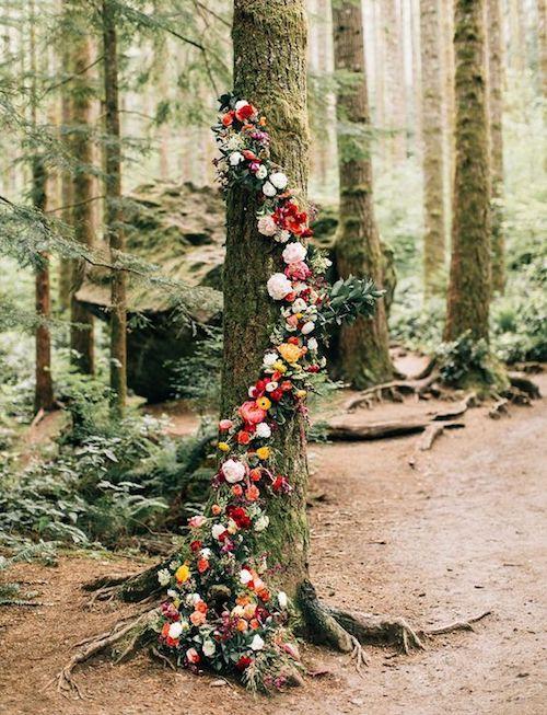 Árbol envuelto en flores como fondo de ceremonia para una boda en el bosque.