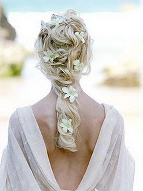 Peinados de novia con flores naturales para una boda en playa.