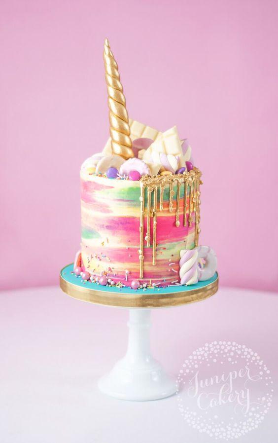 Una tarta desenfadada de buttercream con un unicornio y arco iris de Juniper Cakery.