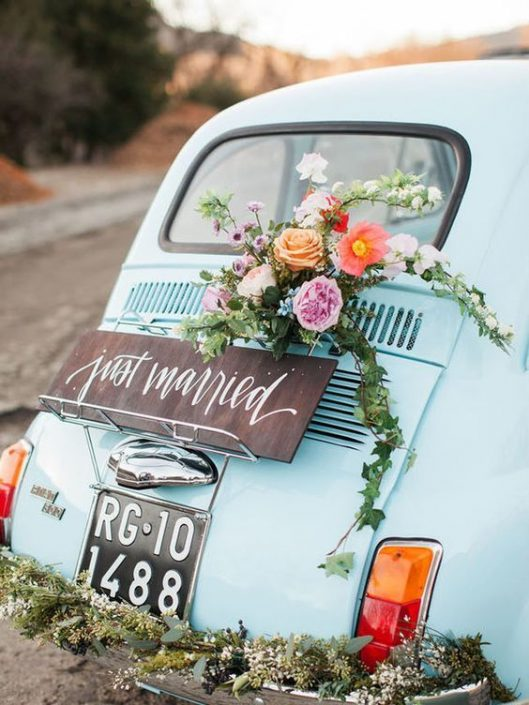 Vintage getaway car that is all kinds of chic adorned with florals and calligraphy.