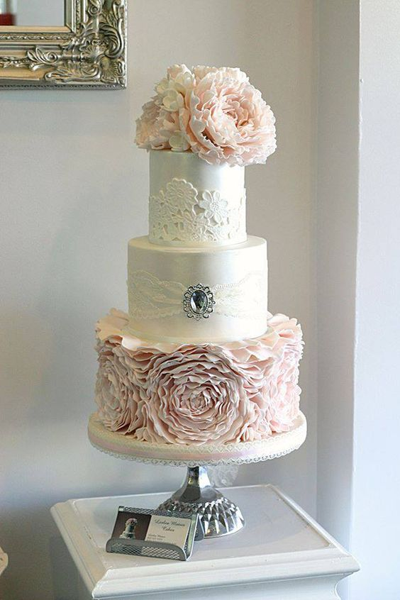 Chic vintage style wedding cake with an old world feel, pink ruffles and a cameo.