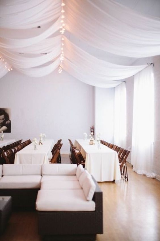 String lights with draped fabric on the ceiling for an all-white modern Hollywood wedding. Photo: Taylor Made Art.