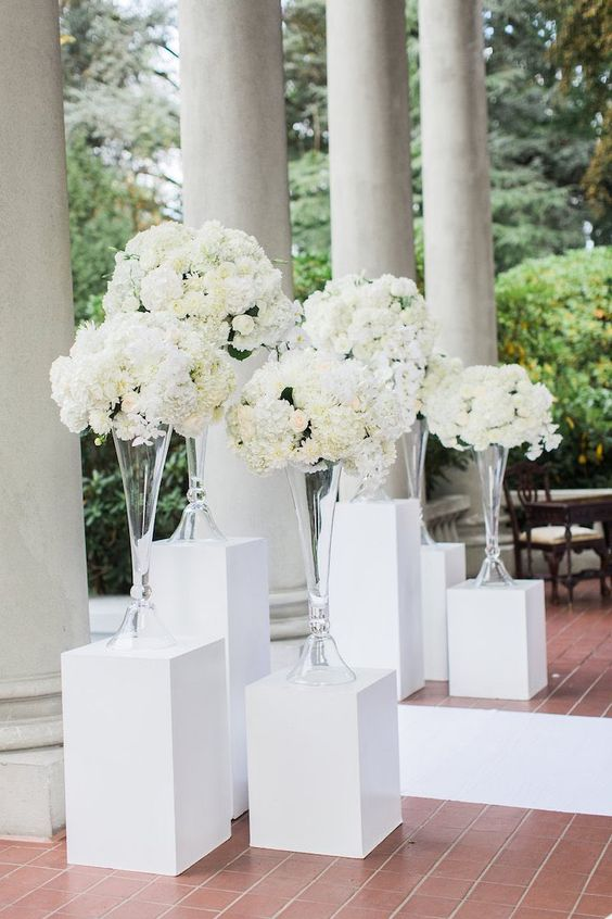 Truly amazing entrance and it really doesn't take much to build. A few white wooden stands, long transparent vases and lots of white gardenias. Ready, get set, go! and wow your guests! Photo: Simply Sweet Photography.