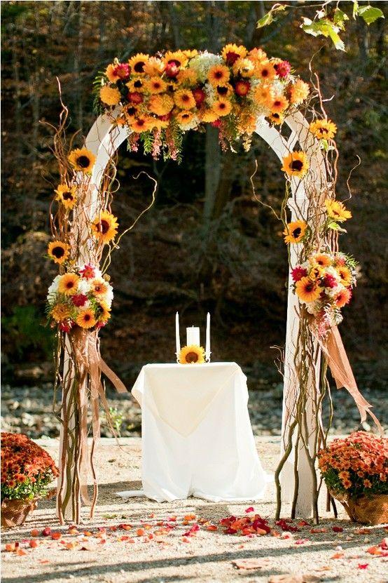 Arco de girasoles que mezcla el rojo, naranja, chocolate, amarillo, verde y vino para una boda en otoño.