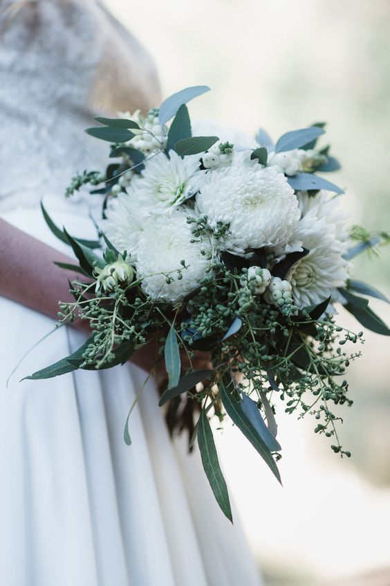Even forest weddings can be donned in all white. Greenery makes for a wonderful complement to the bridal bouquet and the decor. Photo: Niki Photography.