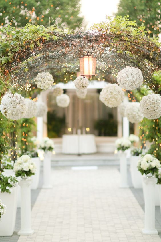 Flank the church pews with white columns and suspend flower balls from the wedding arch for a stunning, elegant and unique look.