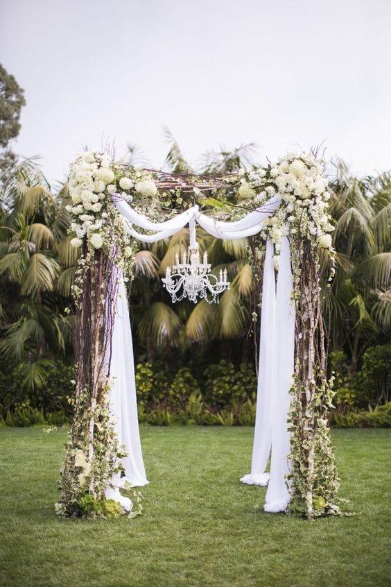 Deco vintage con tela drapeada sobre el arco y un magnífico chandelier.