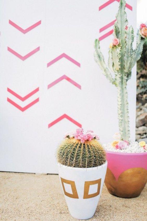 Las flores rosadas de esta decoración con cactus combina a la perfección con el motivo del fondo. Boda en Palm Springs y fotografía de Gideon Photo.
