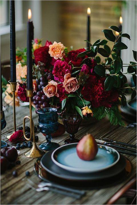 Decadente decoración de mesa con frutas, bayas y velas azul marino.