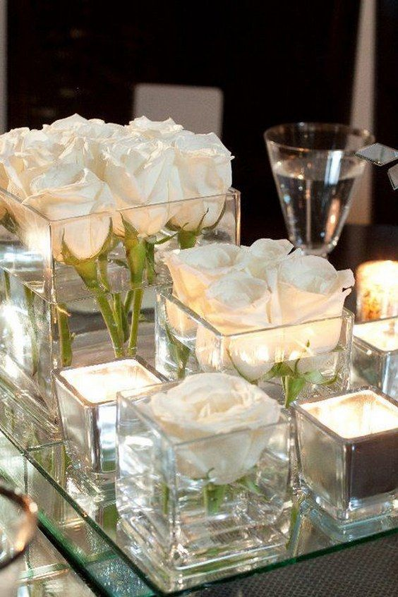 Stunning DIY wedding centerpiece. Here's what you'll need: mirror. 3 or 4 glass containers, candles and votives and white roses. Little trick to keep flowers afloat: add a piece of bubblewrap under them.