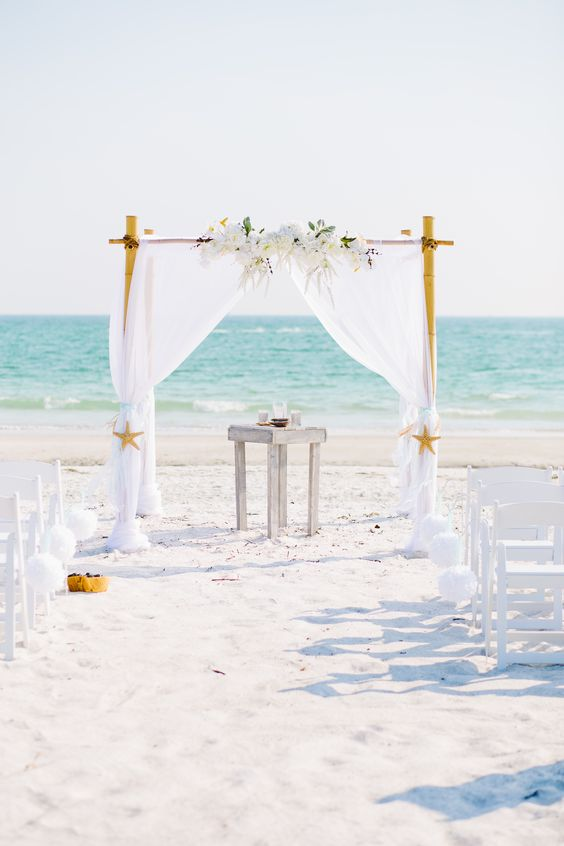 Elegant white beach wedding arch.