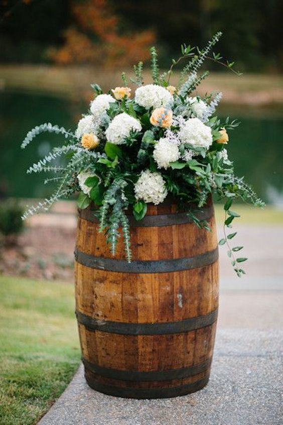 Peach, cream, and greenery flower arrangement atop a wine barrel. Photo: Brandy Angel Photography.