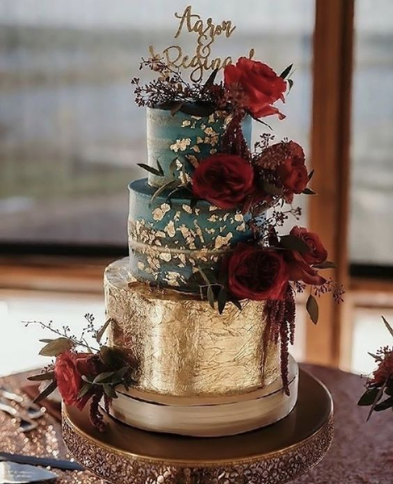 Contrasting roses against a superb gold foil wedding cake atop a band cake plate.