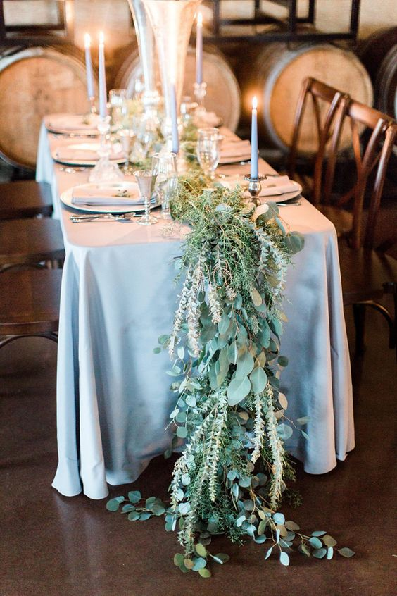 Dusty blue tapered candles and table linen adorned with a greenery table runner. Photo: Ashley Errington Photography.