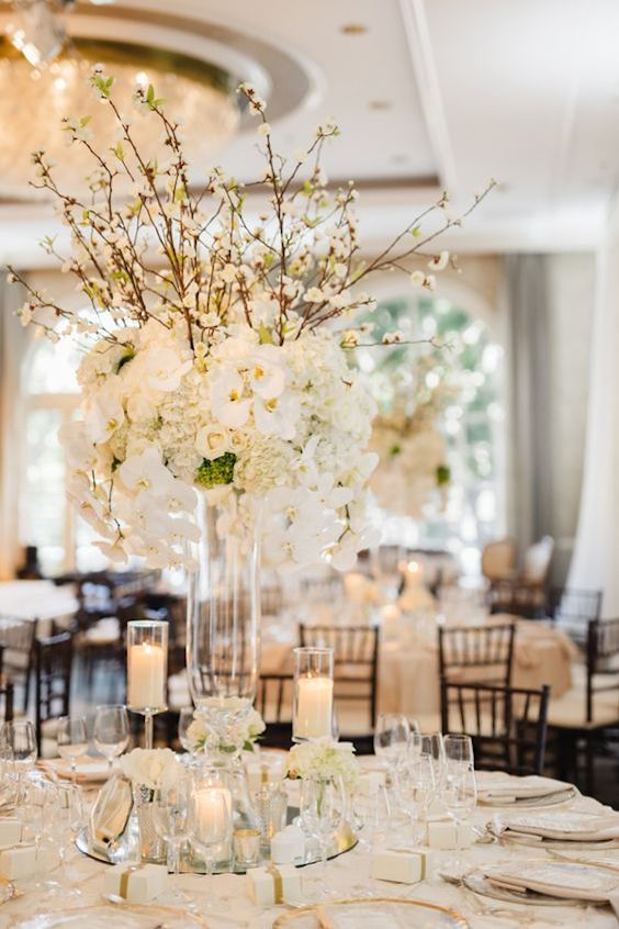 Indoor white wedding at the Four Seasons in Beverly Hills. Notice the mix and match of a tall centerpiece with shorter candle holders on top of a mirror and a sliver of gold on the dinnerware. Jana Williams Photography.