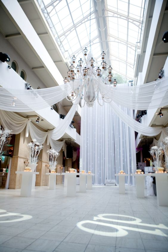 Indoor industrial white wedding decor. Raw spaces are perfect to unleash your creativity and play with geometric and minimalist shapes. Love the drapery and the chandelier.