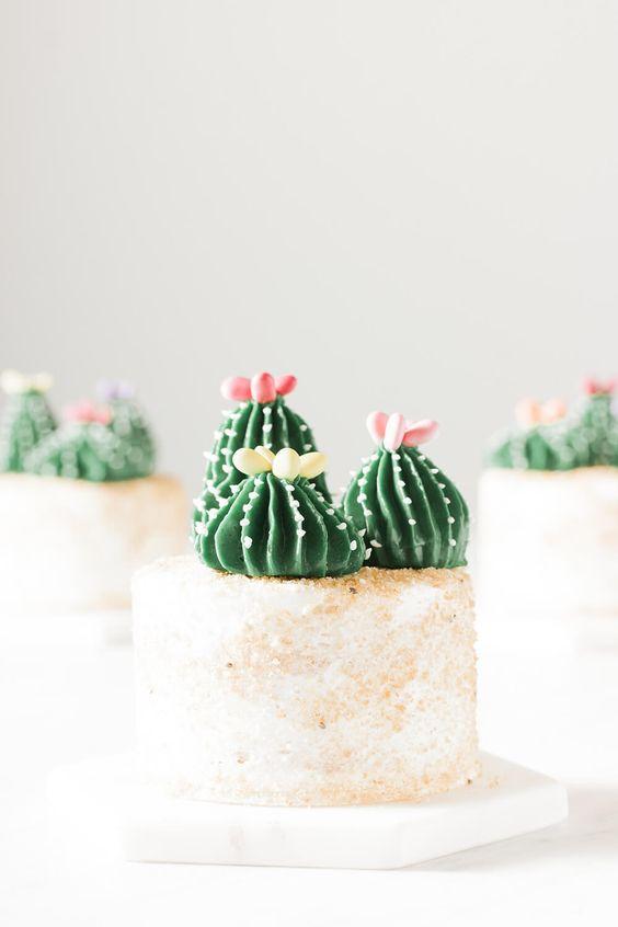 Mini pasteles de vainilla cubiertos con trios de merengue suizo buttercream en forma de cactus sobre arena comestible. ¡Las flores del cactus están hechas con las semillas de girasol revestidas del caramelo de Trader Joe's!
