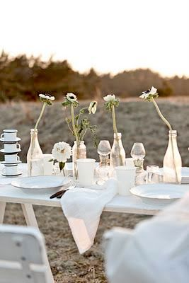 Very rustic chic white table with trestles, bottles and single flowers as centerpieces. Check out the delicate gold filament dishes. Swoon!