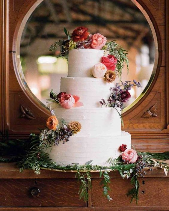 Rustic vintage wedding cake featuring colorful floral decorations and greenery.