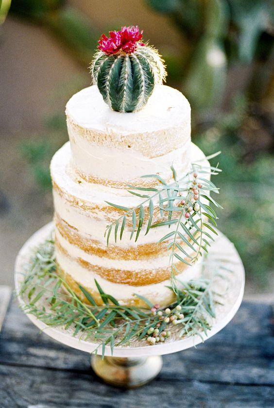 Un topper de cactus es el toque final sobre este pastel blanco semi desnudo. ¡Nos encanta la flor que agrega un estallido de vibrante color!
