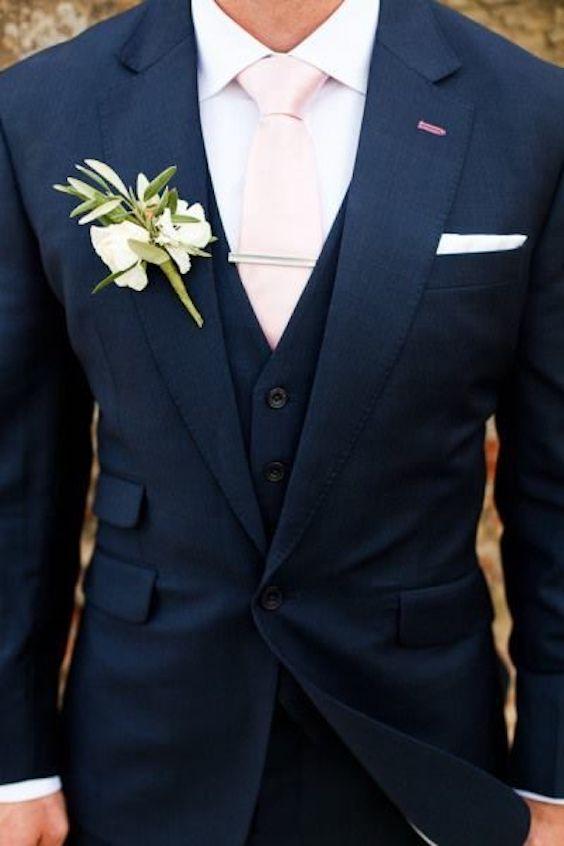 Traje de novio en azul marino y rosa pálido.