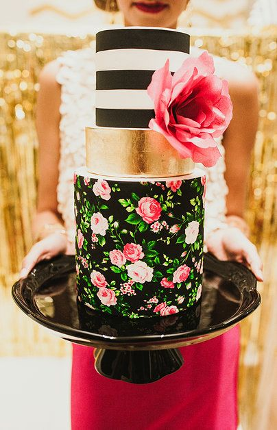 A modern twist on vintage wedding cakes. Gold bands, hand painted floral patterns and black and white stripes. Don't forget the flower!