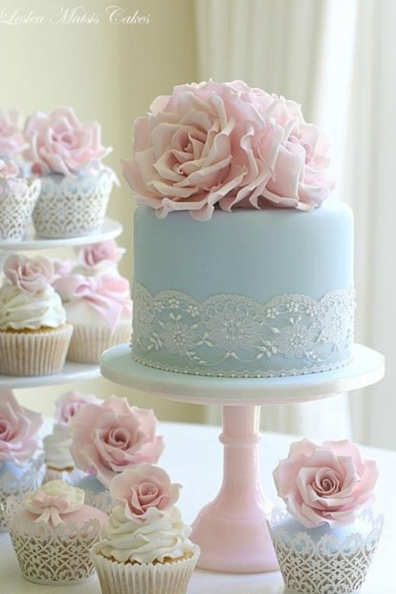Adorable wedding cake accompanied by cupcakes.