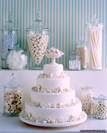 This perfectly designed white beach wedding cake makes us swoon. Surrounded by a gorgeous dessert table decor and white candy.