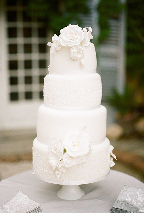 Classic and impressive four-tiered white wedding cake with sugar flower details created by Wedding Cakes by Pamela.