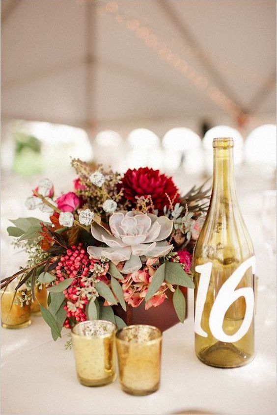 Dreamy tablescape with wine bottle table numbers surrounded by gold mercury votives.
