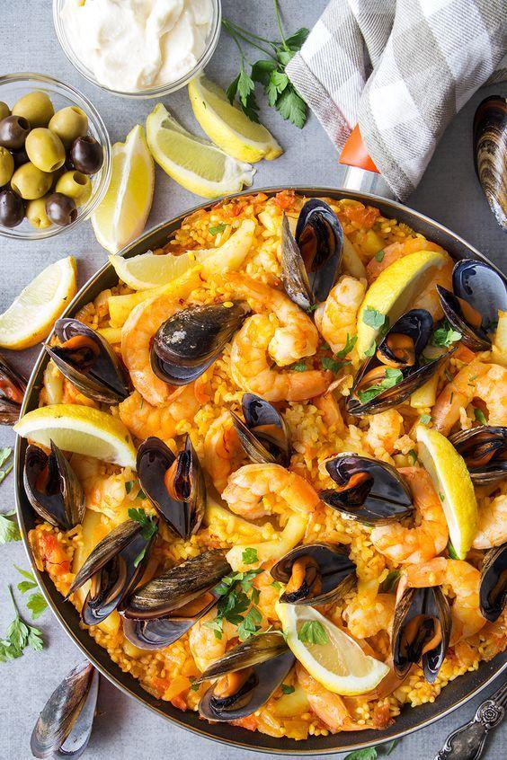 Esta paella de mariscos española cuenta con una capa de azafrán crujiente y arroz con infusión de vegetales cubierto con calamares, mejillones y camarones. Resultado: Invitados felices.