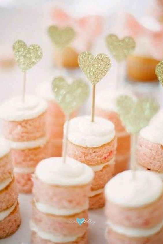 Dainty mini pink cakes with gold heart toppers.