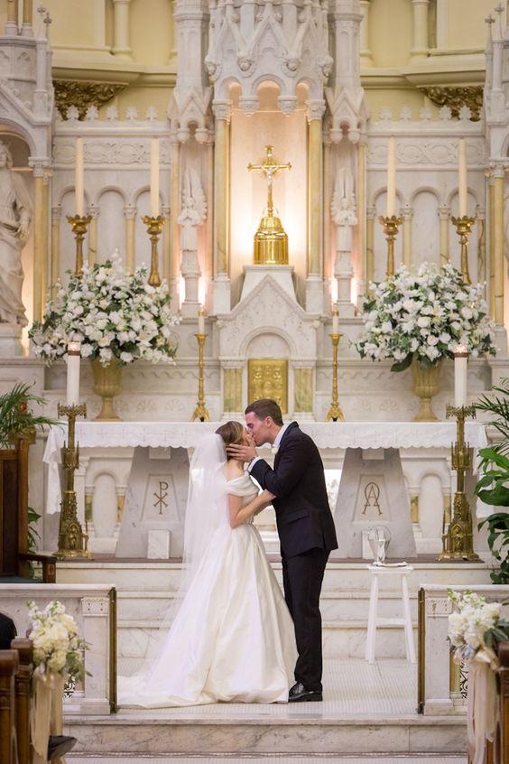 El primer beso de los novios. Ceremonia en la iglesia católica del Sagrado Corazón en Tampa, FL.