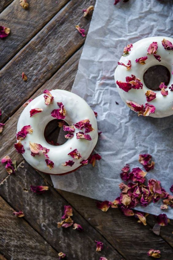 Red velvet doughnuts with a cream cheese glaze and edible rose petals. Recipe by Chef Town.