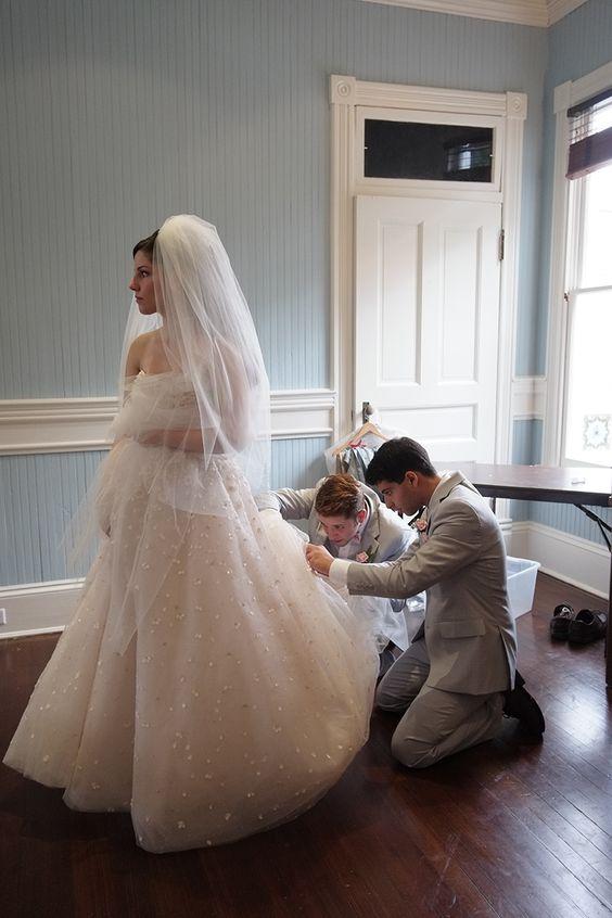 Los caballeros de honor ayudan a la novia con su vestido de Christos Peony.